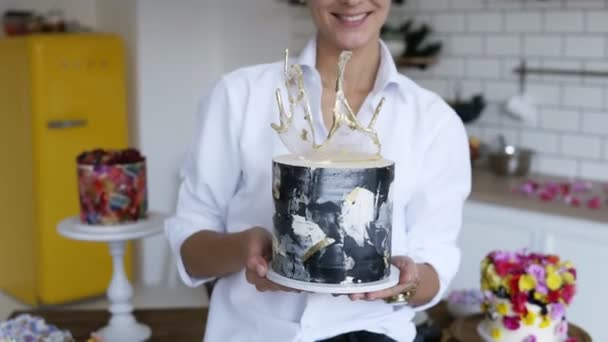 Female confectioner in white shirt presenting modern decorated black and white cake in her kitchen. Yellow fridge and white walls kitchen with fancy decorated cakes on the background