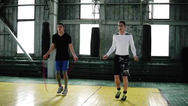 Kaukasische junge Boxer springen mit einem Springseil, während sie sich im Boxstudio aufwärmen. Hochsprung synchron. volle Länge, Vorderansicht