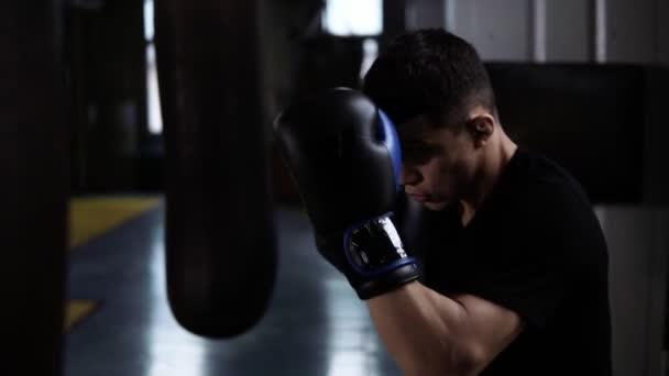 Der junge Mann im schwarzen T-Shirt macht die Schläge, trainiert mit großer schwerer Boxtasche im Fitnessstudio. Starke Schläge, schützendes Gesicht, Block