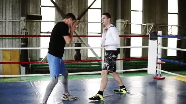 Zwei junge Boxer in legerer Kleidung, die ohne Handschuhe auf dem Ring stehen, trainieren in voller Länge Schläge miteinander. Männer trainieren gemeinsam, trainieren Streiks und Reaktionen. Old-Style Box-Studio-Studio. Zeitlupe