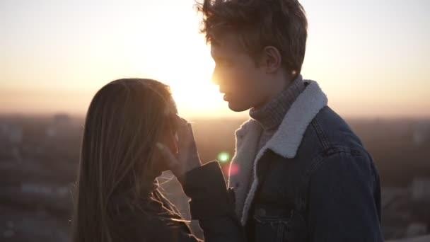 Blondy mladík a její dlouhé vlasy holka stojí na roog během sunrise všeobjímající. Pospolitosti, hladí navzájem a při pohledu na obzoru na cityspace se těší