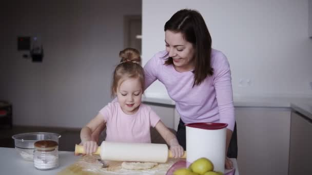 Beautiful young loving mother teaching her cute little daughter rolling out dough with a rolling pin while cooking together at the kitchen. Cooking and having fun