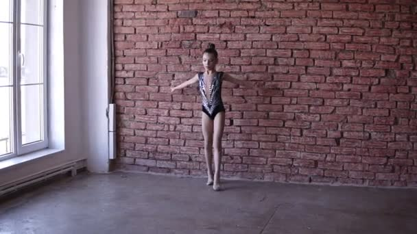 Cute girl engaged in rhythmic gymnastics in artistic bodysuit near the windows. Young gymnast jumping in the gymnastics school or studio