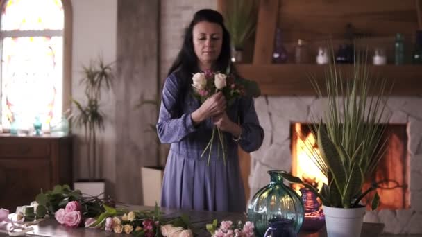 Longhaired female florist in blue dress holding a half made bouquet and adding flowers and plants to composition. Designing, floral workshop, leisure. Blurred picture of fireplace on the background