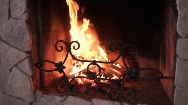 Zavřete a pak vystřelí na dřevo hoří pomalu s pomerančem a žluté ohně plamen v moderní kamenné zdobené krb. Život na venkově. Hořící naštípat dříví v kamenné ohniště ve dne