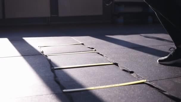 Frau in schwarzen Leggings trainiert im Fitnessstudio beim Steppen, springt auf geteilten Abschnitten auf dem Boden und trainiert schwitzend mit Entschlossenheit Teil der Kickbox-Serie. Füße aus nächster Nähe in Turnschuhen