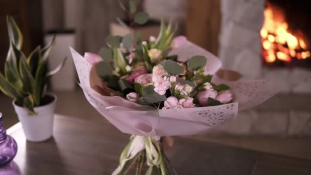 Beautiful bouquet of pastel colors flowers in pink decorative paper stands on the stems on a gray table after the flower masterclass. Flowers decoration design concept. Fireplace on the background