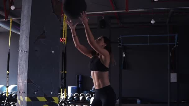 Sideview footage of a young fit woman in black leeggings and bra exercising by throwing a medicine ball up against a wall in a dark coloured modern gym full of equipment on the background