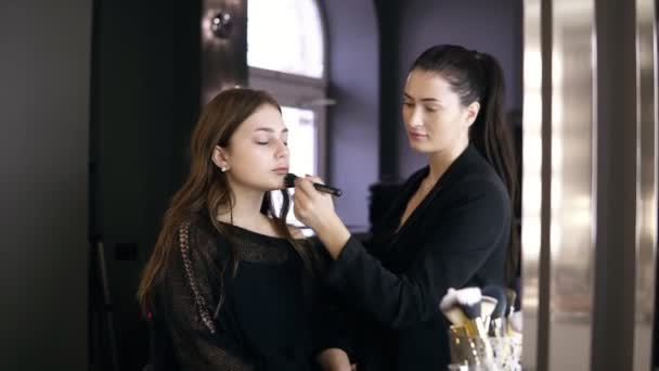 Professional makeup artist in black suit with pony tail applying cosmetic s on models face with a large black make up brush. Young girl in black clothes in the salon doing make-up, apply powder on