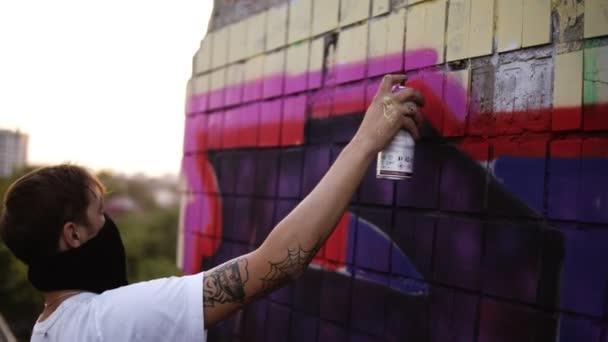 Az aeroszol graffiti művész festése. Férfi Balaclava és fehér póló spray palackot. Fiatal városi festő fedett arcát rajz színes graffiti a városi utcai fal nyáron a