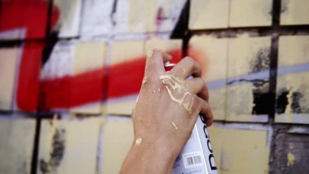 Detailní záběr umělců ručně špinavé v barvě nanášení spreje kreslení červené barevné čáry na zdi budovy ulice. Akce. Pořezané prsty umělce držet sprej plechovka s barevným nátěrem na betonové zdi