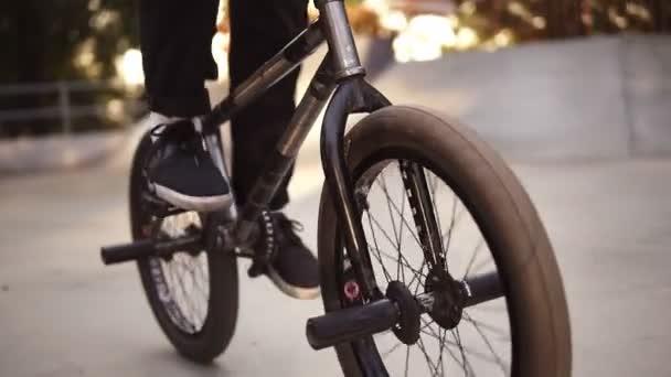 Felismerhetetlen extrém bmx motoros pedálozza a fekete kerékpár egy napos gördeszka parkban a nyáron. Menő fiatal BMX motoros kerékpározás a szabadban. Zárja le a kerekeket. Lassú mozgás.
