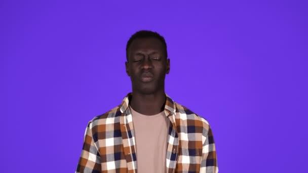 Porträt eines kranken afrikanisch-amerikanischen Mannes im karierten Hemd, der Kieferknochen mit Schmerzen im Gesicht berührt und unter Zahnproblemen leidet, isoliert vor blauem Hintergrund. Konzept der Emotionen