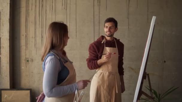 Férfi diák tanul festeni olajfestékkel. Sötét hajú férfi bézs kötényben rózsaszín virágokat rajzol ecsettel, a női mentor részletes magyarázatával. Műhely művészeti stúdióban