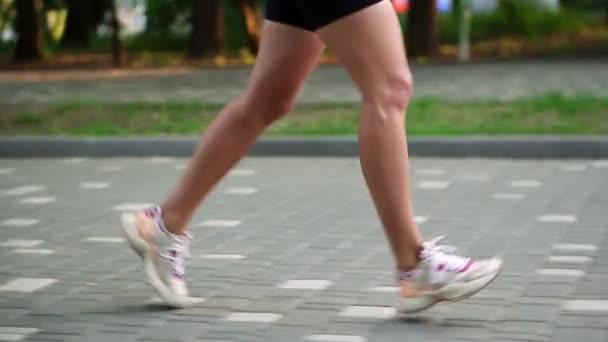 V parku běhají atleti. Fitness žena běhá venku. Cvičení na dlažbě parku. Zdravý, fitness, wellness životní styl. Sport, kardio, koncepce cvičení. Boční pohled. Zpomalený pohyb
