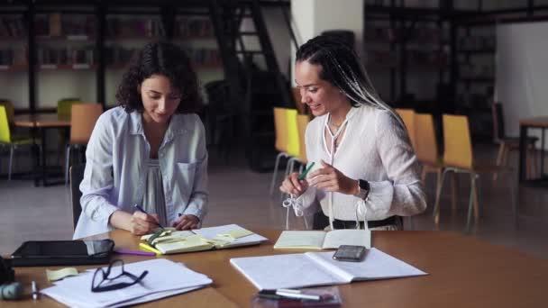 Dvě atraktivní, bělošky sedící u stolu a psající poznámky, sdílející nápady. Ženy v bílých blůzách sedí v moderní knihovně a společně pracují na projektu