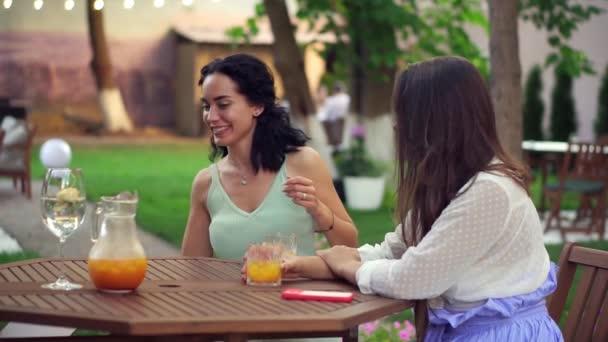Dvě ženy sedící v kavárně venku - povídání, sdílení zpráv, brunetka pokládání notebook na stůl a propagace něco