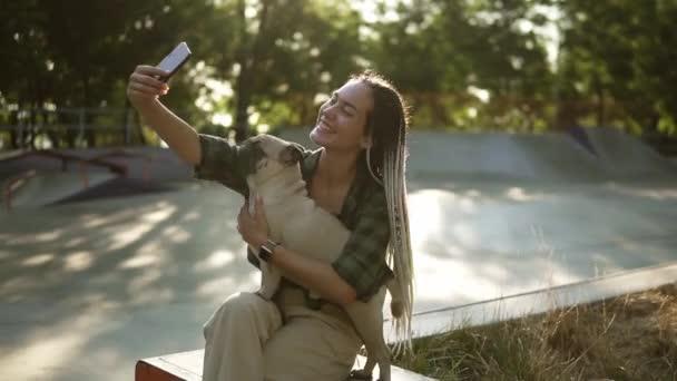 Vidám lány csinál szelfi fotó aranyos mopsz kölyökkutya zöld városi parkban gazdaság okostelefon nyáron
