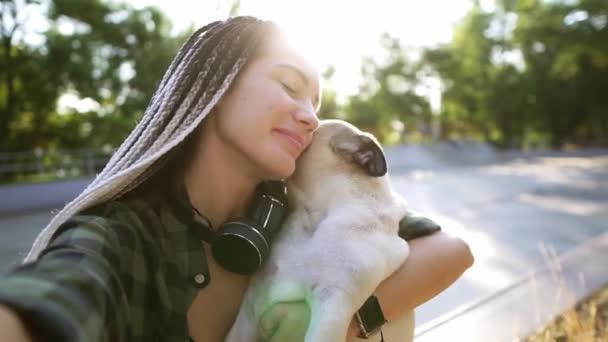 Egy cuki bézs mopsz kiskutya próbálja lenyalni az arcát. Egy nő kamerát és kancsikat tart.