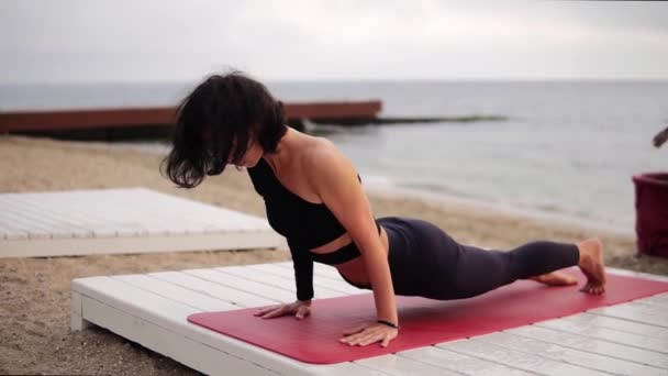 Relaxační žena v černém sportovním oblečení cvičit jógu na podložce před mořem v dopoledních hodinách - provádění bhujangasana póza