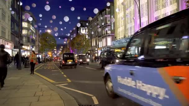 Christmas lights, red buses and black cabs on busy Oxford Street. London, UK