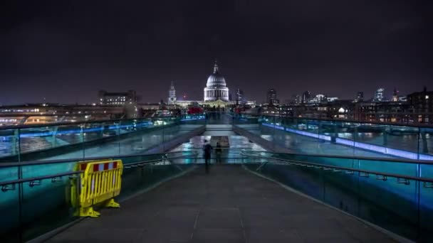 People crossing the Millennium Bridge linking the City of London with the South Bank between St Paul Cathedral and Tate Modern art gallery