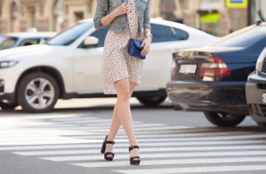 close up of woman legs walking on crosswalk. The woman is wearing shoes on high heels.