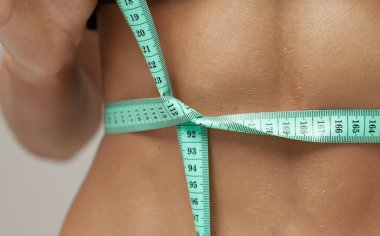 Athletic slim woman measuring her waist by measure tape after a diet over gray background