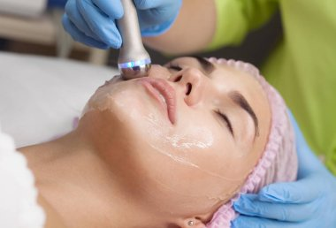 Beautiful woman getting radio frequency lifting on her face. Professional beautician doing anti-wrinkle facial treatment. Concept of skin care and correction of skin texture.