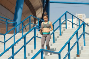 Fit asian woman running up the stairs in the city