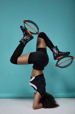 young fitness girl posing on kangoo training boot.