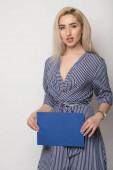 fiatal, mosolygós nő gazdaság egy üres papírlapot a reklám