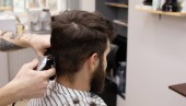 Stílusos fodrászat vágás haj az ügyfél a fodrászboltban. Szakálla ember egyre fodrász a szalonban.