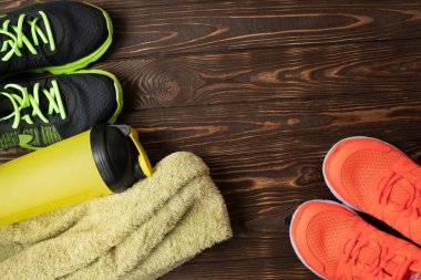 Sports equipment - sneakers, water6 towel. Sport background on wooden floor, top view .