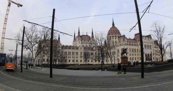 Hungarian parliament building exterior and city traffic with yellow tram