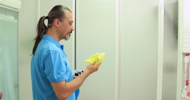 Muž čisticí sprchový koutem okno