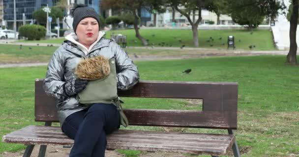 Portrét ženy sedí na lavičce v parku a mají silný žaludek bolest rukou na břiše