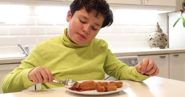 Porträt eines kleinen Jungen, der Chicken Nuggets isst und in der Küche in die Kamera blickt