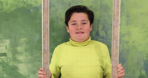 Porträt eines gutaussehenden Jungen, der durch einen Rahmen schaut und vor einer Kamera alberne Gesichter macht