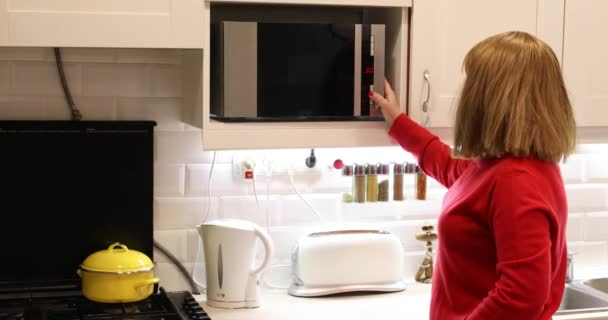 Woman in kitchen using microwave oven
