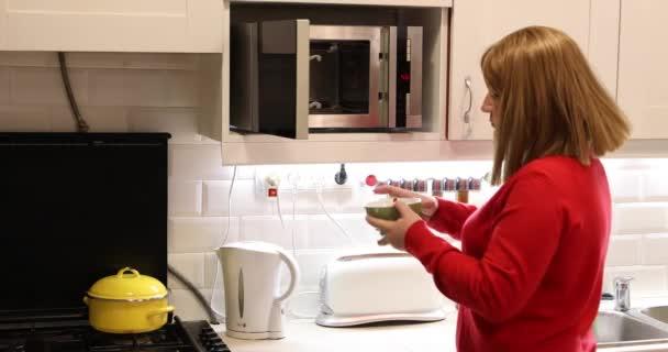 Žena v kuchyni používat mikrovlnnou troubu