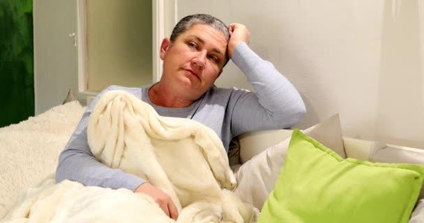 Porträt einer Frau mittleren Alters mit Grippe, die auf einem Sofa liegt und sich zu Hause ausruht