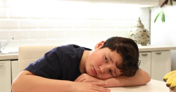 Ritratto di un infelice preteen ragazzo seduto in cucina da solo.