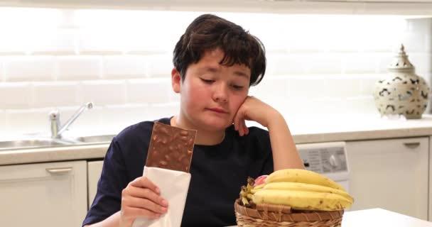 Gyermek közötti választás gyümölcsök, banán egészséges élelmiszer édességek, csokoládé, egészségtelen ételek