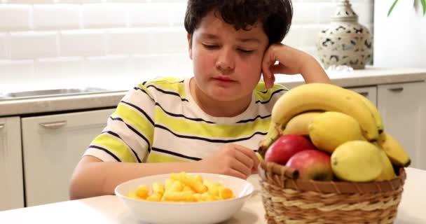Tini fiú választása között gyümölcsök és chipek 2