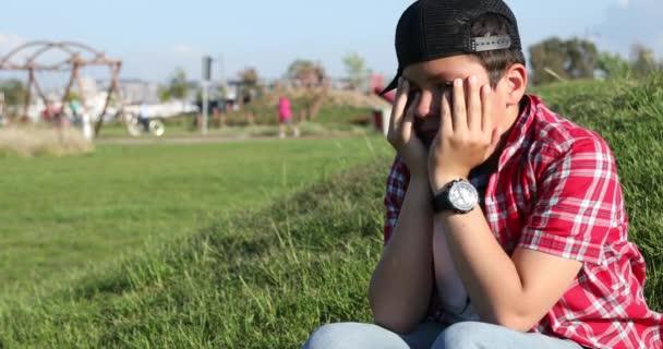 Triste preteen ragazzo piangere al parco da solo