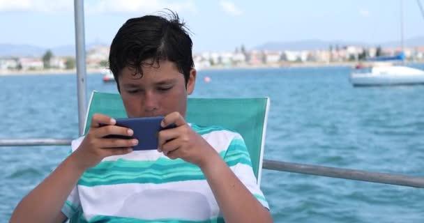Mladý chlapec na lodi pomocí smartphone 5