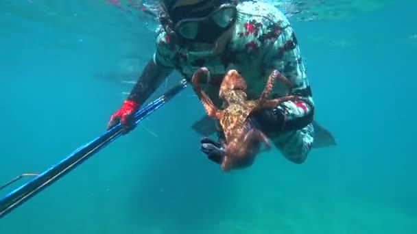 Man in a suit underwater hunter caught octopus 2