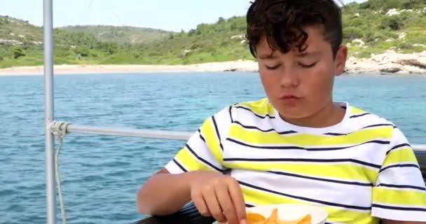 Fiatal fiú eszik burgonyaszirom a jachtfedélzet nyári időszakban 6