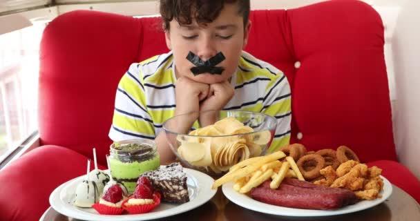 Mund eines kleinen Jungen mit Klebeband mit Fast-Food-Teller verschlossen 4